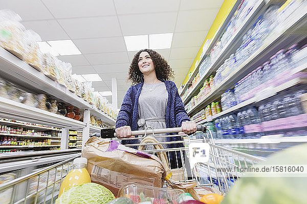 Woman pushing shopping cart in supermarket aisle