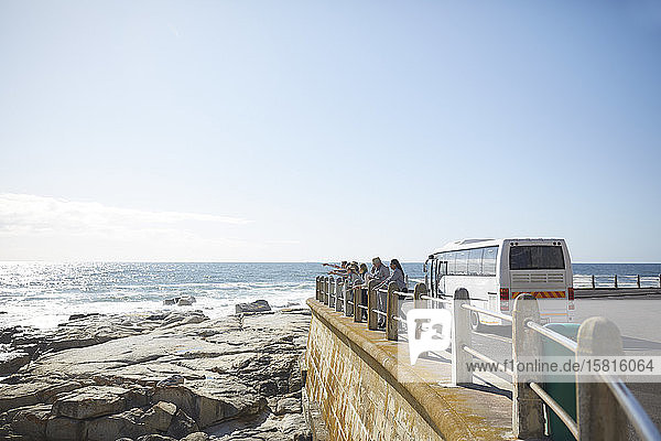 Tourists looking at sunny ocean view outside tour bus Tourists looking at sunny ocean view outside tour bus