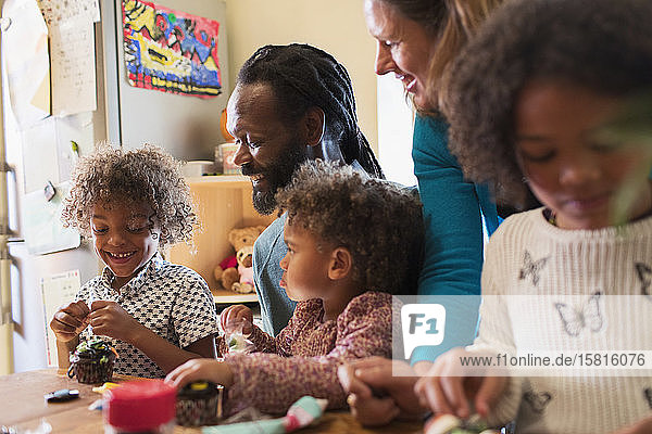 Multiethnic family decorating cupcakes at table Multiethnic family decorating cupcakes at table