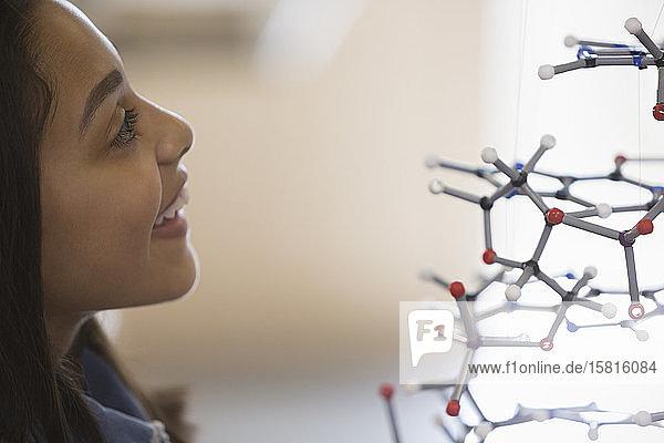 Curious girl student examining molecular structure Curious girl student examining molecular structure