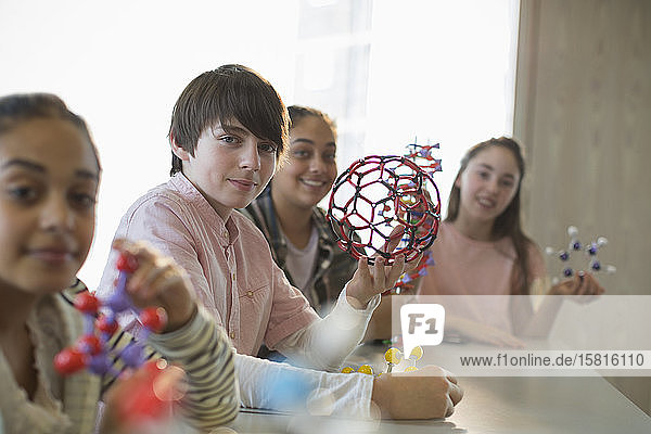 Portrait confident students holding molecular structures in laboratory classroom
