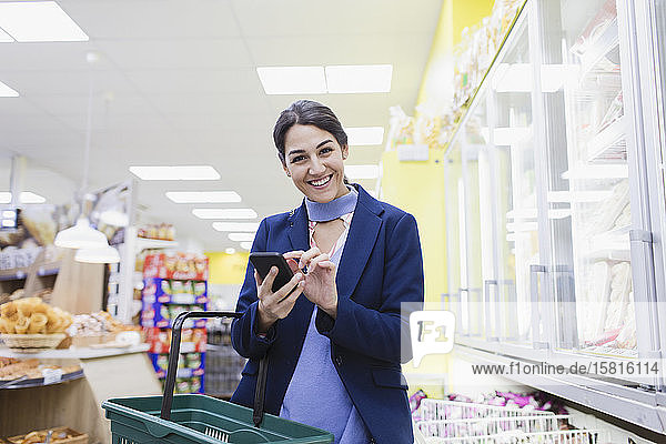 Portrait smiling  confident woman with smart phone shopping in supermarket Portrait smiling, confident woman with smart phone shopping in supermarket