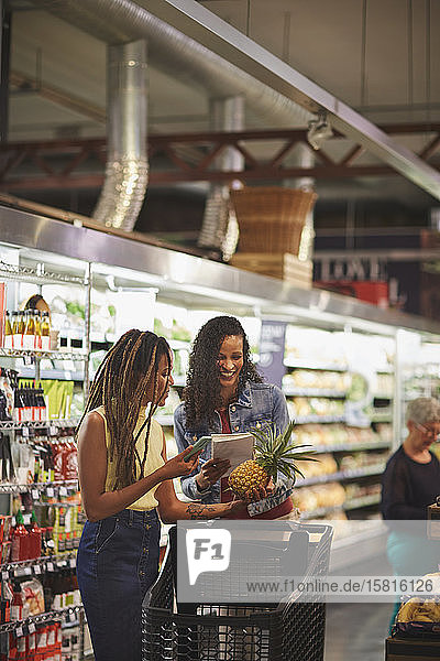 Women with shopping list and smart phone shopping in supermarket