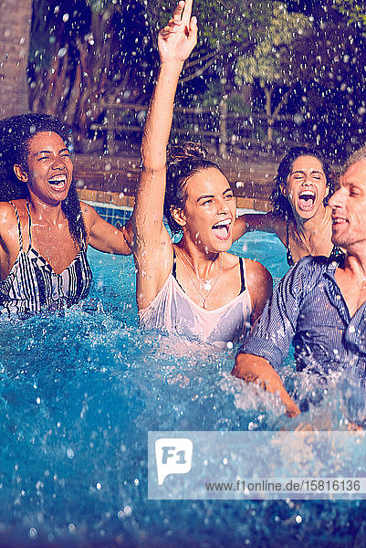 Enthusiastic friends playing and splashing in swimming pool