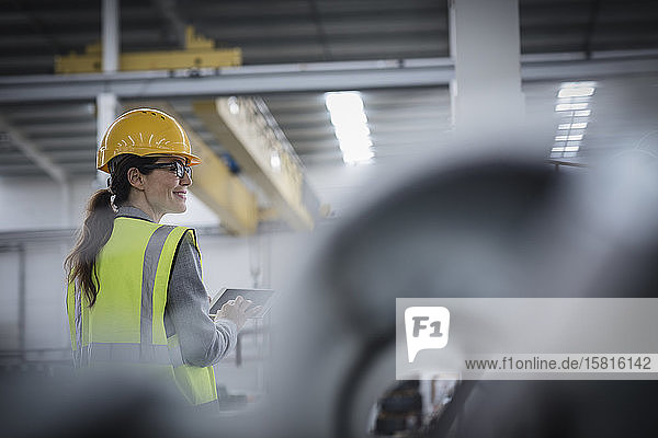 Confident female worker using digital tablet in steel factory
