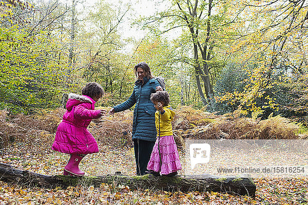 Mother and daughters playing on fallen log in autumn woods