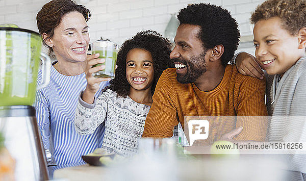 Smiling multi-ethnic family drinking healthy green smoothie in kitchen