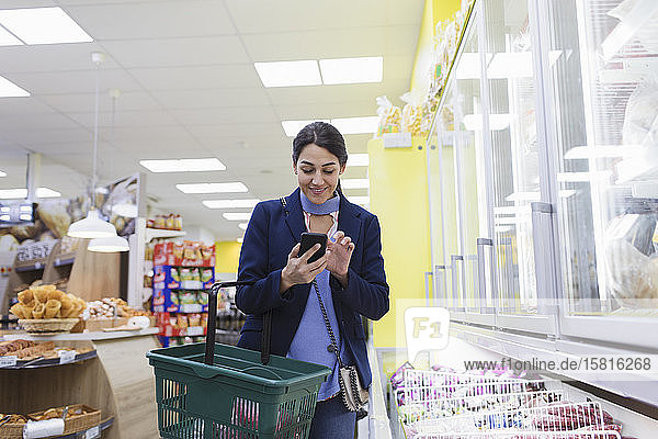 Woman with smart phone working in supermarket