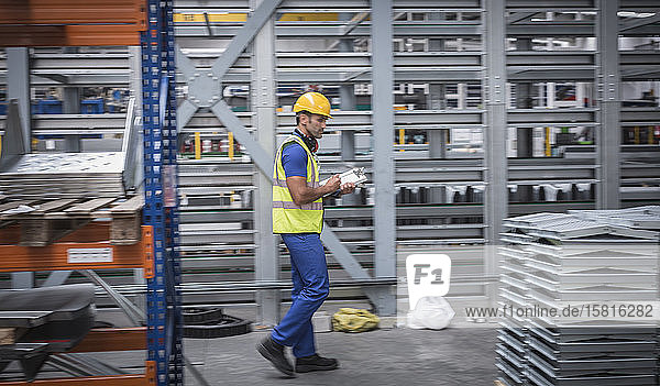 Male supervisor with clipboard checking inventory in steel warehouse Male supervisor with clipboard checking inventory in steel warehouse