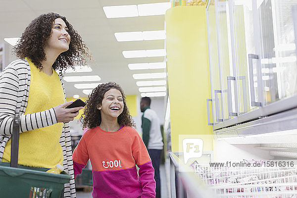 Happy mother and daughter shopping frozen food in supermarket