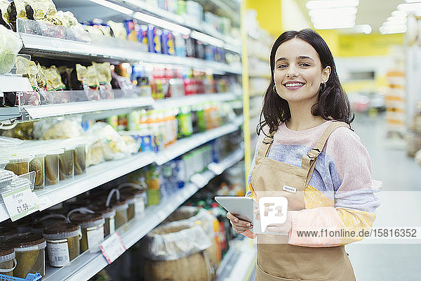 Portrait confident  smiling female grocer with digital tablet in supermarket