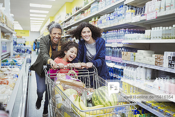 Playful multi-generation women pushing shopping cart in supermarket aisle