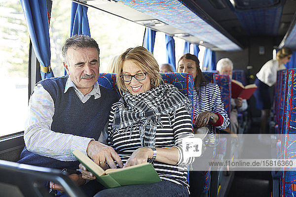 Active senior couple tourist reading book on tour bus Active senior couple tourist reading book on tour bus