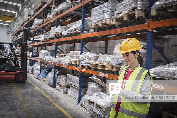 Female worker with clipboard checking inventory in warehouse
