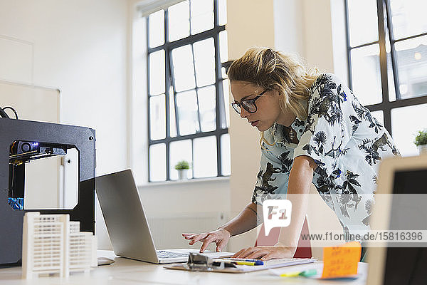 Female designer working at laptop next to 3D printer in office Female designer working at laptop next to 3D printer in office