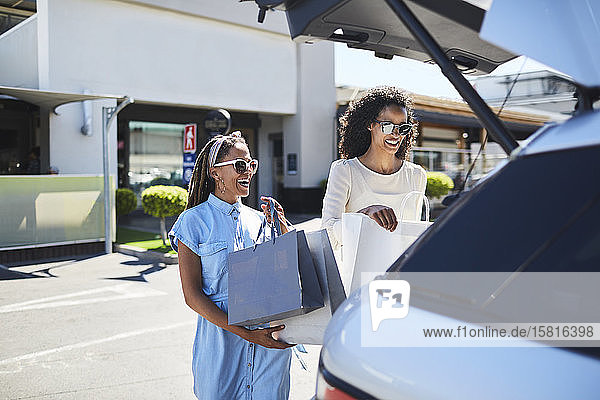 Frauen laden auf einem sonnigen Parkplatz Einkaufstüten in den Kofferraum eines Autos