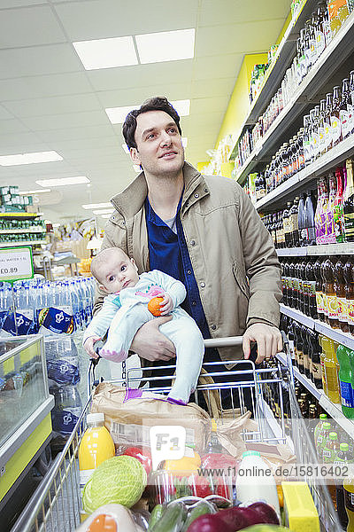 Father and baby daughter shopping in supermarket