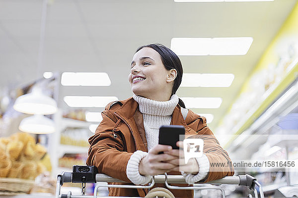 Smiling  confident woman with smart phone shopping in supermarket