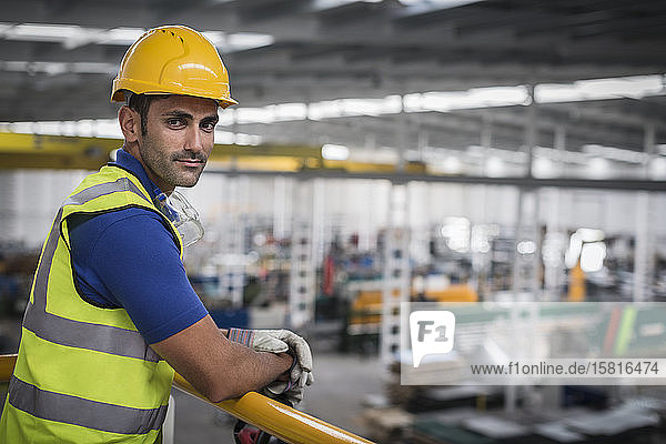 Portrait confident male supervisor leaning on platform railing in factory Portrait confident male supervisor leaning on platform railing in factory