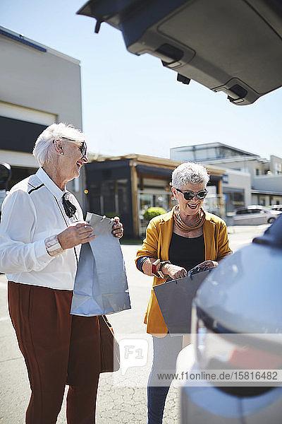 Glückliche Seniorinnen laden Einkaufstüten hinten in einen SUV auf dem Parkplatz eines Einkaufszentrums