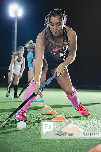 Focused young female field hockey player practicing sports drill on field
