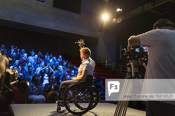 Female speaker in wheelchair on stage waving to audience
