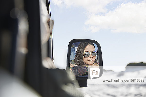 Smiling young woman wearing sunglasses in side-view mirror of car Smiling young woman wearing sunglasses in side-view mirror of car