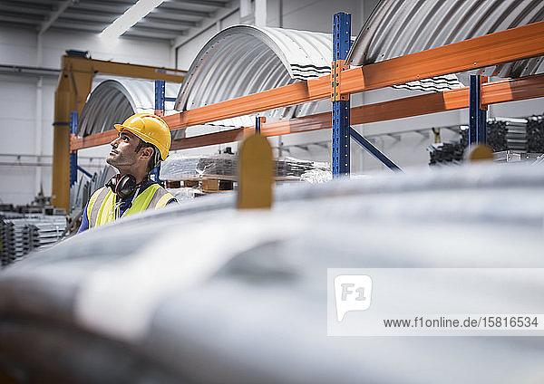 Male worker looking up in steel factory Male worker looking up in steel factory