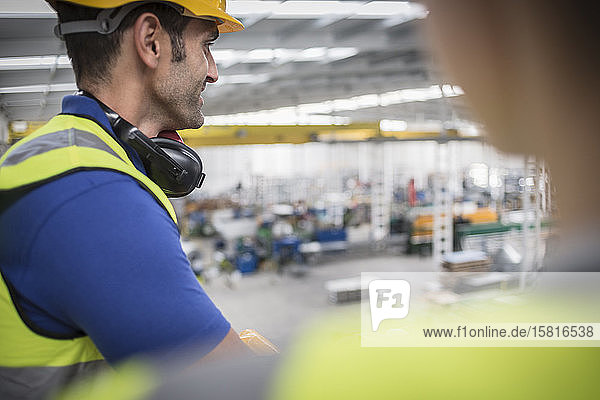 Male worker on platform watching factory Male worker on platform watching factory
