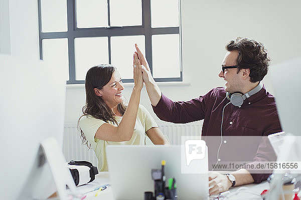 Computer programmers high-fiving at laptop in office