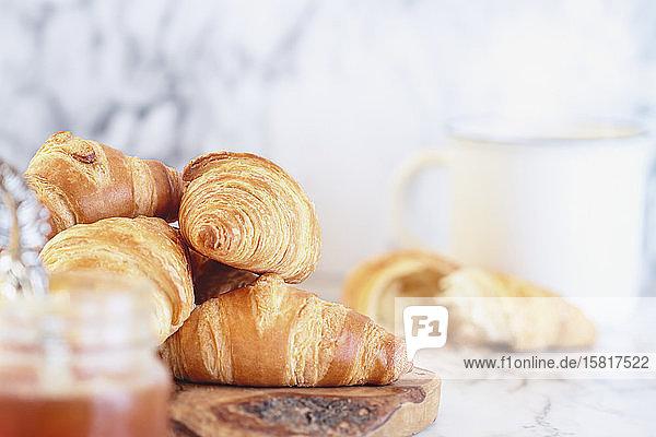 Croissants mit Konfitüre und Kaffee zum Frühstück
