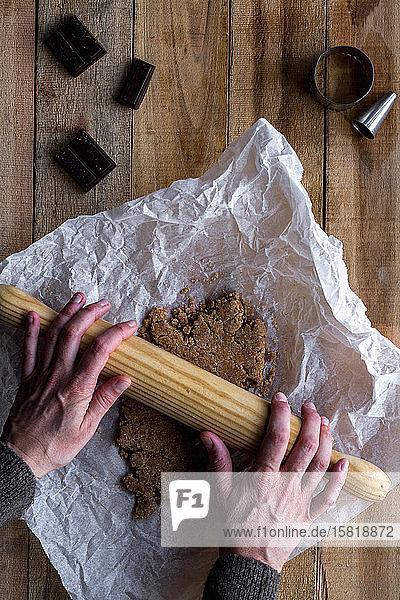 Person  die Schokoladenteig mit einem Nudelholz auf weißem Backpapier ausrollt