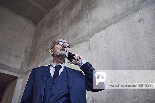 Leitender Geschäftsmann am Telefon  niedriger Blickwinkel
