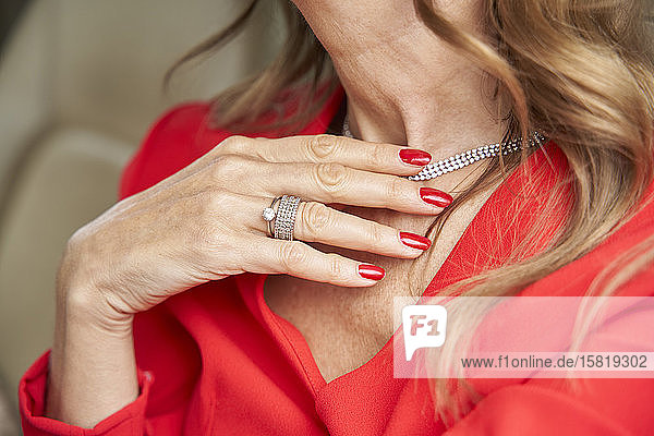 Crop view of mature woman with red nails
