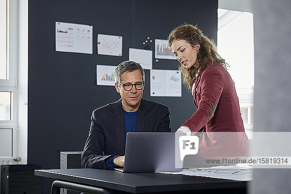 Businessman and businesswoman working together on laptop in office