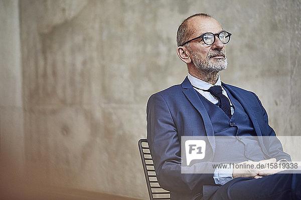 Leitender Geschäftsmann auf dem Stuhl sitzend  nachdenklich