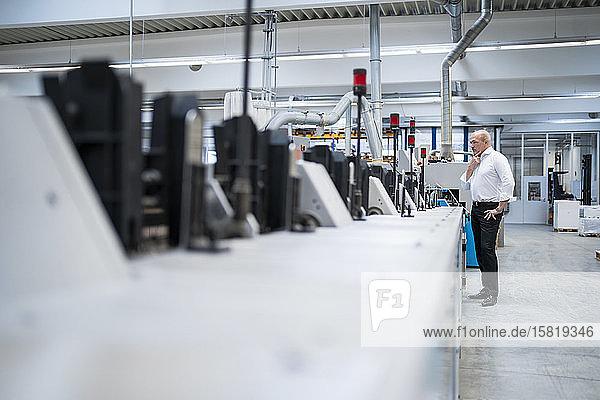 Geschäftsmann  der in einer Fabrik an einer Maschine steht
