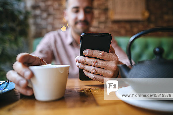 Nahaufnahme eines Mannes in einem Cafe mit Teetasse und Handy