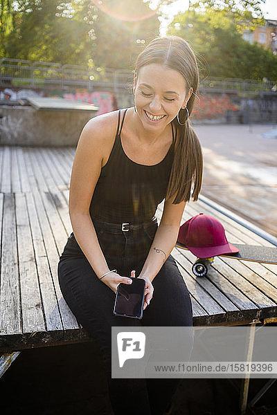 Junge lachende Frau mit Smartphone im Skatepark