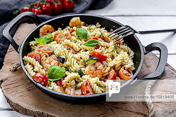 Pan ofready-to-eatpasta with tomatoes  shrimps  zucchini and basil