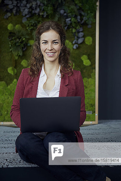 Portrait of smiling businesswoman sitting on the floor in green office using laptop