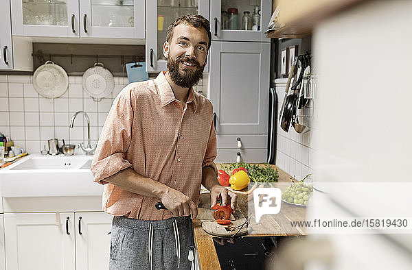 Junger Mann steht in der Küche  schneidet Tomaten  lächelt