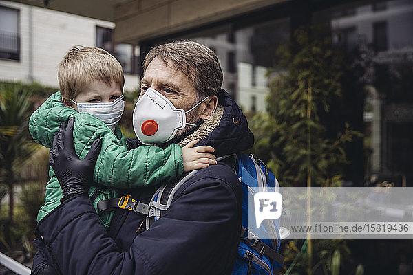 Vater trägt Sohn,  beide tragen Schutzmasken,  im Freien