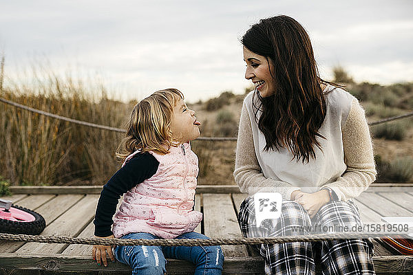 Happy mother and cheeky daughter sitting on a boardwalk in the countryside