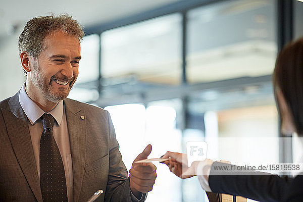 Porträt eines lächelnden Geschäftsmannes  der an der Hotelrezeption eincheckt