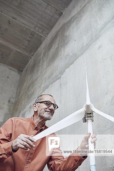 Leitender Ingenieur arbeitet an Windenergielösungen und betrachtet Windturbine