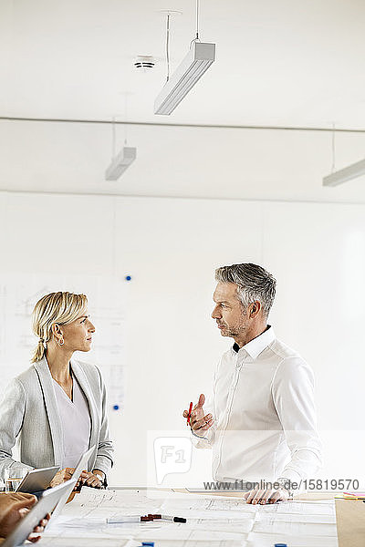 Leitender Geschäftsmann und Frau leiten Workshop im Amt