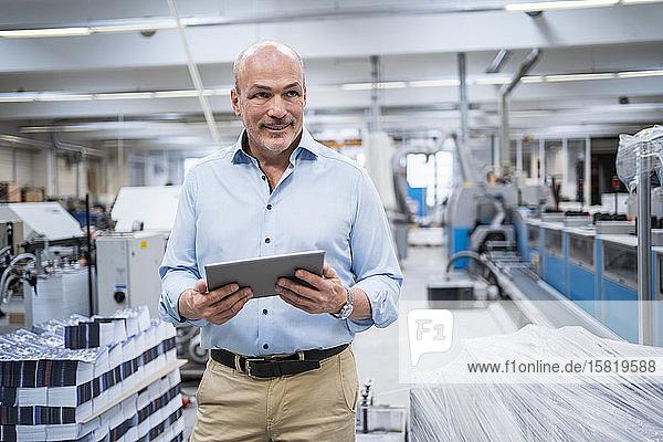 Porträt eines selbstbewussten Geschäftsmannes in einer Fabrik mit Tablette