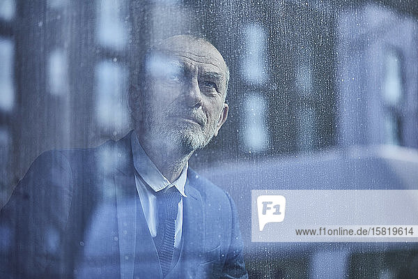 Leitender Geschäftsmann  der aus dem Fenster schaut