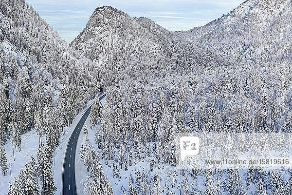 Deutschland  Bayern  Luftaufnahme von Bergautobahn und schneebedecktem Wald im Winter